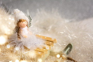 Toy angel on small sledge with Christmas background