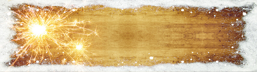 Silvester background panorama banner long - frame made of snow with snowflakes, sparklers and lights on rustic wooden texture, top view with space for text