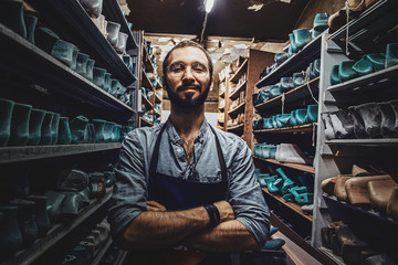 Bearded young cobbler in glasses is posing for photographer at dark shoe form storage.