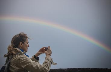 personne photographiant un arc-en-ciel