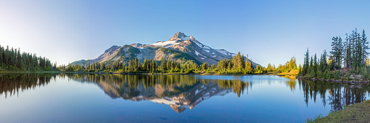 Foto op Canvas Panoramafoto s Volcanic mountain in morning light reflected in calm waters of lake.