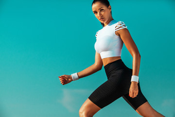 Fototapeta Sporty young woman and fit athlete runner running on the sky background. The concept of a healthy lifestyle and sport. Woman in black and white sportswear. obraz