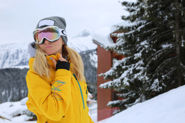 Beautiful ski woman in yellow jacket posing at the slope in Courchevel France.