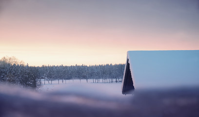 christmas background shiny sunset scenery with winter forest and hut with snowy roof