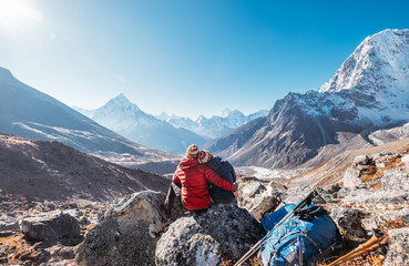 Embracing Couple on the Everest Base Camp trekking route near Dughla 4620m. Backpackers left Backpacks and trekking poles and enjoying valley view with Ama Dablam 6812m peak  and Tobuche 6495m