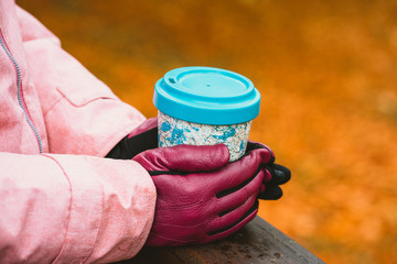 Hands in gloves holds a cup of herbal tee with defocused autumn golden colored leaves in background