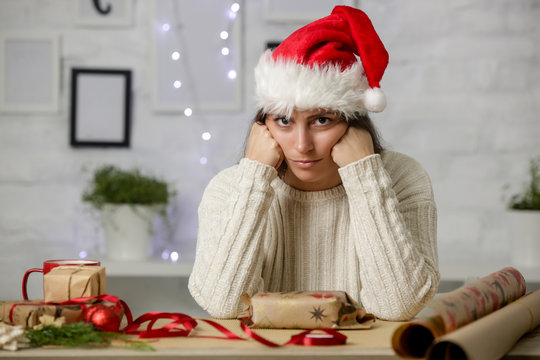 Depressed frustrated woman wrapping Christmas gift boxes, winter holiday stress concept