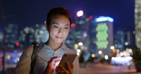 Wall Mural - Woman use of smart phone in Hong Kong city at night