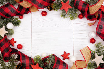 Christmas frame of ornaments, branches, burlap and red and black buffalo plaid ribbon. Overhead...