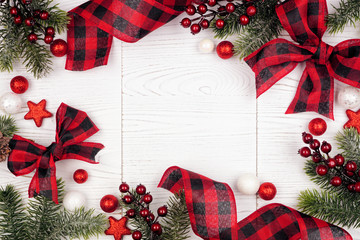 Tuinposter Buffel Christmas frame of ornaments, branches and red and black checked buffalo plaid ribbon. Top view on a white wood background.