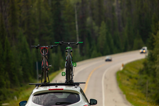 Selective focus on bicycles on roof top while driving on the highway. Safety road equipment for bike transport. Road and woods at background