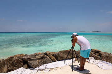 Young man taking picture of tropical beach with azure sea water