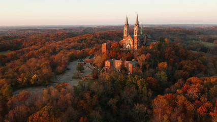 Aerial view of a church on the top of hill and autumn forest, red foliage . Fall season, autumn colors. Countryside, Wisconsin. Drone shots at sunset Wall mural