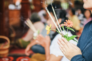 An asian woman keep a lotus, candles and incense sticks in hands for praying respect to the buddha statue on New year