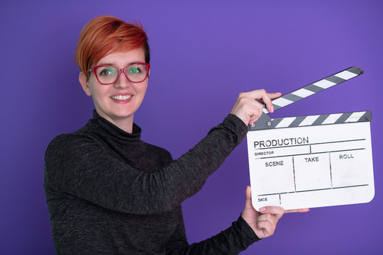 redhead woman holding movie  clapper on purple background