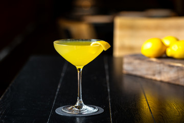 fresh yellow alcohol cocktail with lemon at a restaurant interior, dark background
