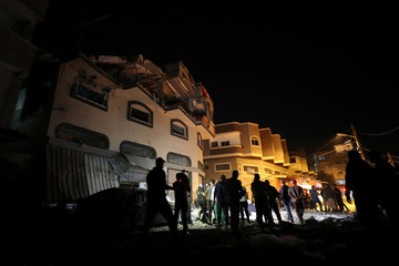 People gather around the home of Palestinian Islamic Jihad field commander Baha Abu Al-Atta after it was hit by an Israeli strike that killed him in Gaza City