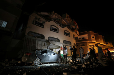 People and members of the media gather around the home of Palestinian Islamic Jihad field commander Baha Abu Al-Atta after it was hit by an Israeli strike that killed him in Gaza City