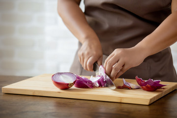 Woman hands slicing red onion in kitchen