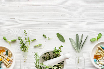 Apothecary of natural wellness and self-care. Herbs and medicine on white wooden background top...