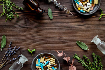 Apothecary of natural wellness and self-care. Herbs and medicine on dark wooden background top view...