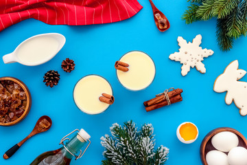 Ingredients for New Year drink eggnog - eggs, milk, cinnamon on blue background top view pattern