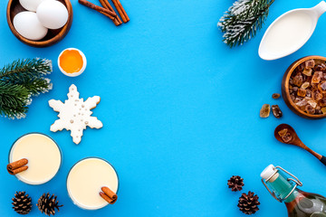 Ingredients for New Year drink eggnog - eggs, milk, cinnamon on blue background top view frame copy space