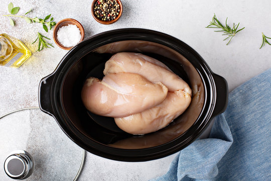 Raw chicken breast in a slow cooker ready to be cooked