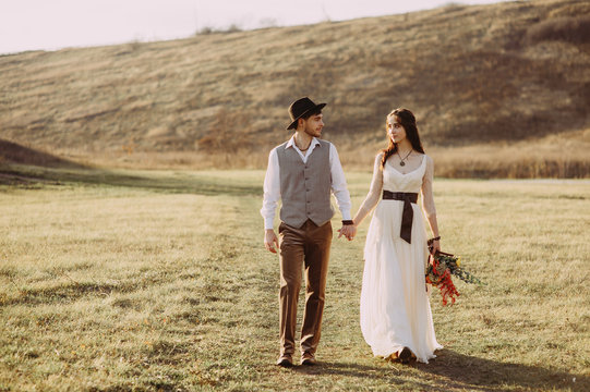 Happy husband and wife. Wedding day. Beautiful nature. Walk during the photo session. They smile at each other. Holding hands