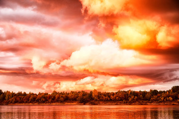 Sky with fantastic, amazing, stormy, disturbing red clouds over the river on a summer or autumn...