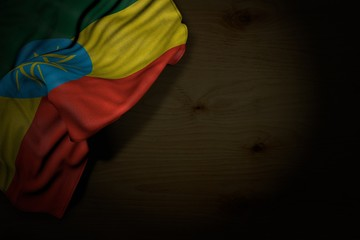 pretty dark picture of Ethiopia flag with large folds on dark wood with empty place for content - any celebration flag 3d illustration..