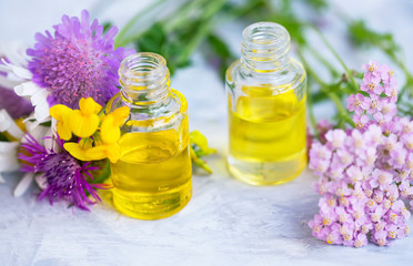 Aromatherapy oil bottles with flowers and green leaves, botanical natural alternative beauty,