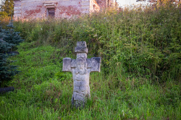 Stone cross with the carved face of the Savior near the Church of Tikhon Zadonsky in the village of Korotsko in Valday