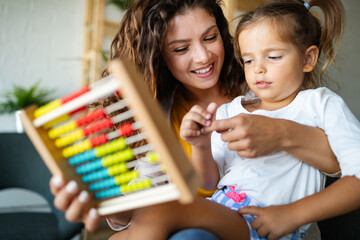 Beautiful woman and kid girl playing educational toys and having fun