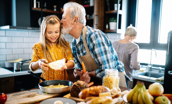 Happy young girl and her grandfather cooking together in kitchen