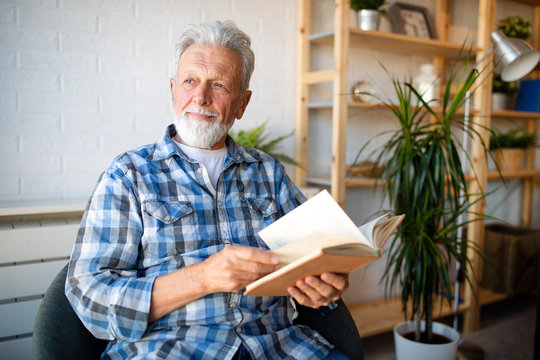 Happy senior man reading book at home