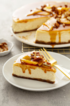 Apple caramel pecan cheesecake with dripping sauce, a slice on a plate