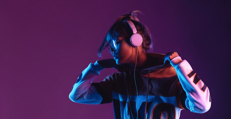 Hipster igen teen pretty fashion girl model wear stylish glasses headphones enjoy listen new cool music mix stand at purple studio background in trendy 80s 90s club blue party light, profile view Fotobehang
