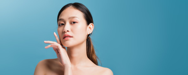 Portrait of confident beautiful asian woman with hand beside face and looking to camera isolated on blue color background with studio shot.Skincare for healthy face concept. Wall mural