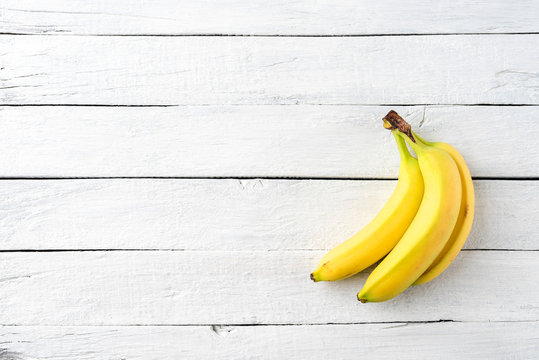 Bunch of bananas on white wooden background. Fruit background