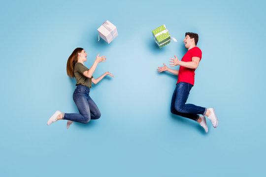 Full length profile side photo of two crazy married people students celebrate 14-february jump holiday throw gift box falling wear casual style clothing sneakers isolated blue color background