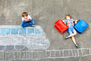 Two little kids boys having fun with train picture drawing with colorful chalks on asphalt. Children having fun with chalk and crayon painting. going on vacations and travel. Friends with suitcases