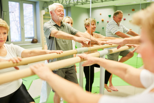 Seniors at the physiotherapy on ballet bar