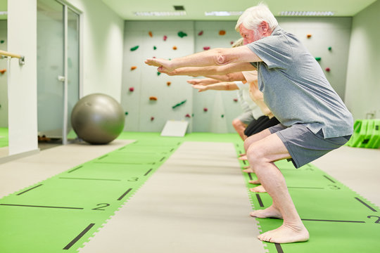 Senior group in fitness class trains leg muscles