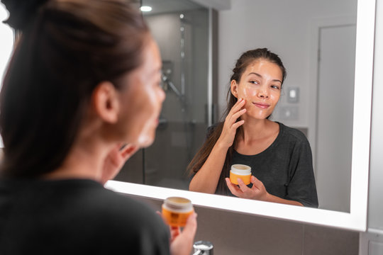 Skin care woman putting face mask product cleaning skincare beauty lifestyle - Asian woman looking in LED mirror in bathroom applying facial cleanser lotion.