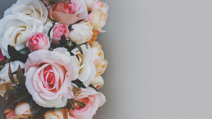 Bouquet of artificial pastel color flowers on gray background, top view with copy space