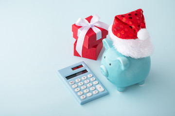 Christmas piggy bank with calculator on pastel blue background