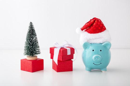 Piggy bank with christmas hat, gift box, christmas tree