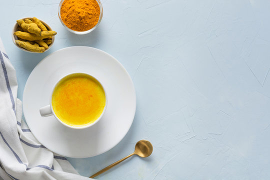 Cup of ayurvedic golden turmeric latte milk with curcuma powder on blue. Space for text or recipe. Healthy drink for immunity. Top view. Natural food