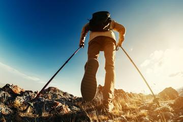 Fototapeta Hiker goes with trekking poles uphill obraz